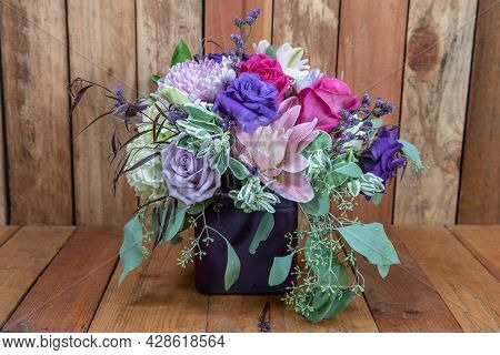 Beautiful Bouquet Of Arranged Pink Chrysanthemum, Roses, And Stargazer Flowers In A Vase Given As An