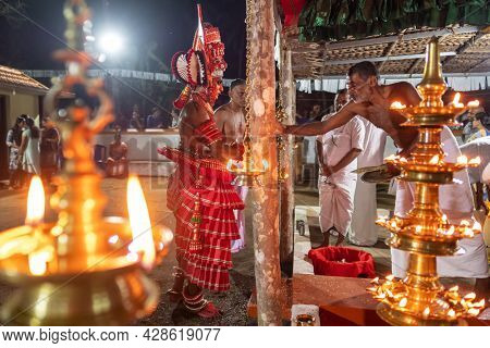 Payyanur, India - December 4, 2019: Theyyam artist perform with fire during temple festival in Payyanur, Kerala, India. Theyyam is a popular ritual form of worship in Kerala, India