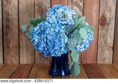 Beautiful Bouquet Of Arranged Blue Hydrongea Flowers In A Blue Vase Given As An Emotional Sentiment.
