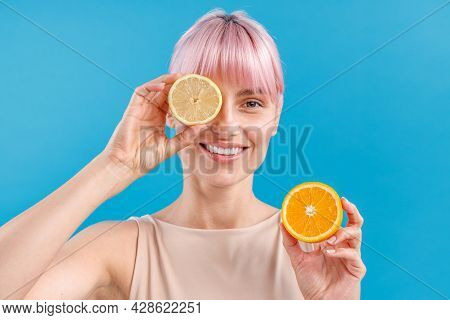 Portrait Of Cheerful Woman With Pink Hair Holding Half Of Fresh Orange And Covering Her Eye With Lem