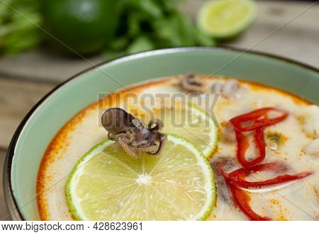 Fresh Tom Yum Soup Close-up: Baby Octopus On A Slice Of Lime, Chili Peppers In Tom Yum Soup