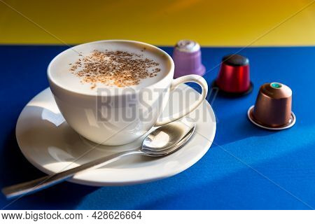 White Cup Of Cappuccino, Espresso Coffee Served With Pods And Capsules On Blue Background. Side View