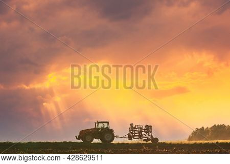 Tractor On Road In Spring Season. Beginning Of Agricultural Spring Season. Cultivator Mounted On Tra