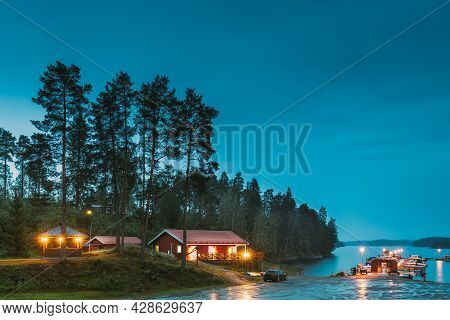 Sweden. Beautiful Red Swedish Wooden Log Cabin House On Rocky Island Coast In Summer Night Evening.