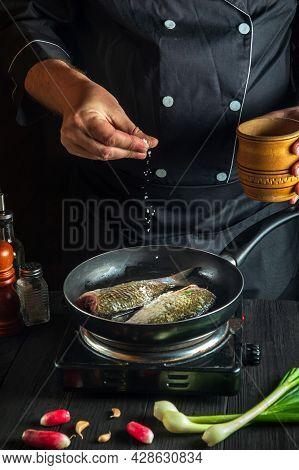 Cook Or Chef Prepares Fresh Fish In Pan Sprinkling Salt With Ingredients. Preparing To Cook Fish Foo
