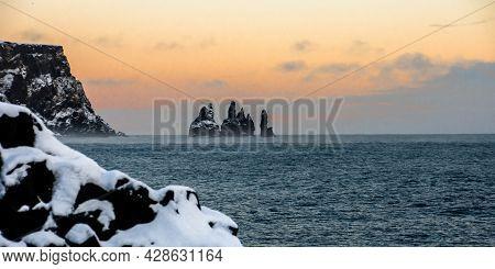 Frozen Black And White Sunset In Reynisfjara Volcanic Beach During The Wintertime. Basalt Sculpture