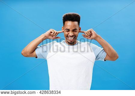 Annoyed And Irritated Displeased Young African American Guy In Trendy T-shirt Covering Ears With Ind