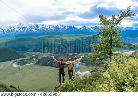 A Group Of Happy Friends Of Three People And A Dog Are Hugging Each Other In The Mountains. Travel A