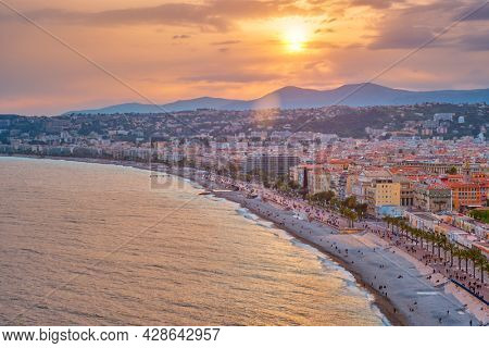 Picturesque scenic view of Nice, France on sunset. Mediterranean Sea waves surging on the beach, people are relaxing on the beach, cars driving the road. Nice, France