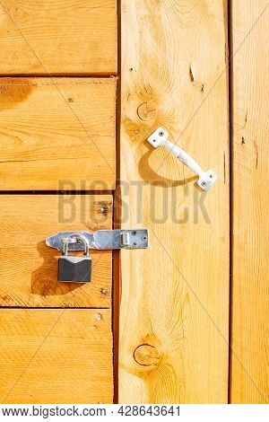 A Small Metal Padlock Hangs On The Closed Wooden Door Of The House, A Shed Made Of Wooden Boards Wit
