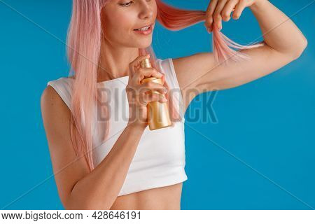 Close Up Shot Of Young Woman Applying Moisturizing Spray To Her Pink Hair Ends While Standing Isolat