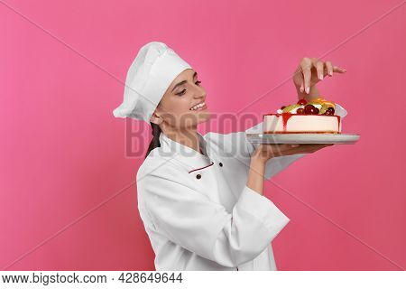Happy Professional Confectioner In Uniform Decorating Delicious Cake On Pink Background