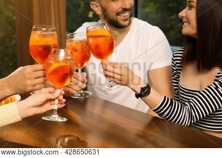 Friends Clinking Glasses Of Aperol Spritz Cocktails At Table, Closeup