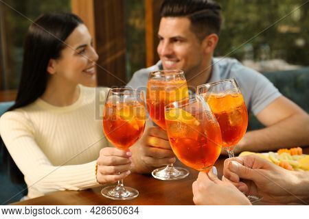 Friends Clinking Glasses Of Aperol Spritz Cocktails At Table, Focus On Hands
