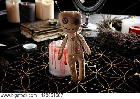 Voodoo Doll Pierced With Pins Near Candle On Table Indoors. Curse Ceremony