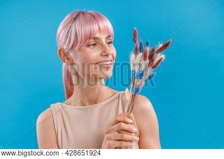 Joyful Woman With Pink Hair Smiling And Holding Dried Flowers Of Neutral Colors In Her Hand, Posing