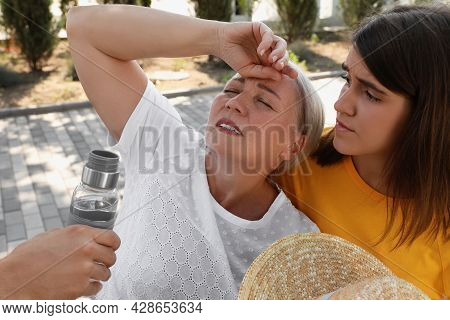 People Helping Mature Woman On City Street. Suffering From Heat Stroke