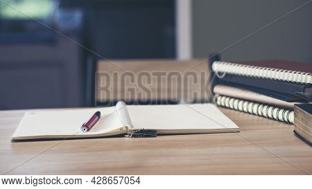 Desk For Student Education Concept. Book For Study For Exam. Stack Of Book, Diary And Pen Placed On