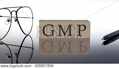 Close-up Of Good Manufacturing Practice. Gmp Wooden Blocks On Black Background With Glasses And Pen