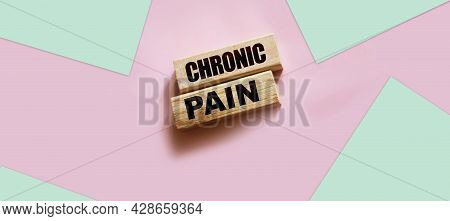 Chronic Pain Words On Wooden Blocks On Pink With Copyspace. Medicine Healthcare Concept.