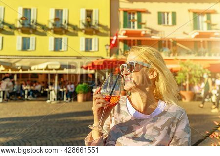 Woman Tourist Drinking A Cocktail By The Lakefront Corniche In An Open Pub Of Ascona Historic City I