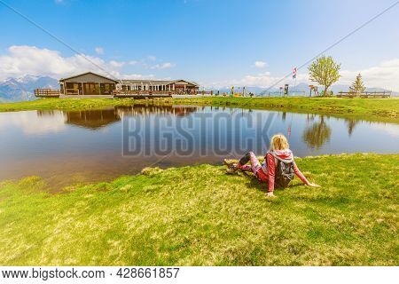 Trekking Woman In Sporty Dress, Resting And Enjoying Tamaro Mount In Switzerland. Swiss Pond In Fopp