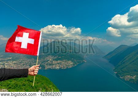 Female Hand Holding A Swiss Flag On Top Of Lugano Lake In Switzerland. Aerial View Lookout From Mont