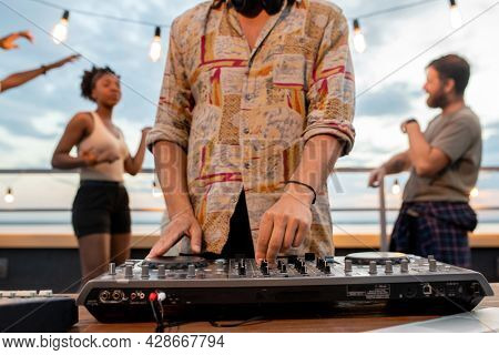 Deejay in shirt mixing sounds while young people dancing on background at rooftop party