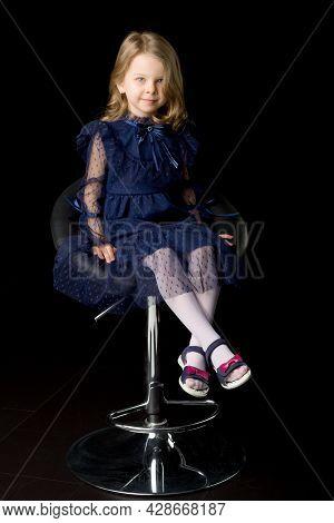 Cute Lovely Little Girl Sitting On High Chair. Full Length Shot Of Charming Smiling Blonde Girl Wear
