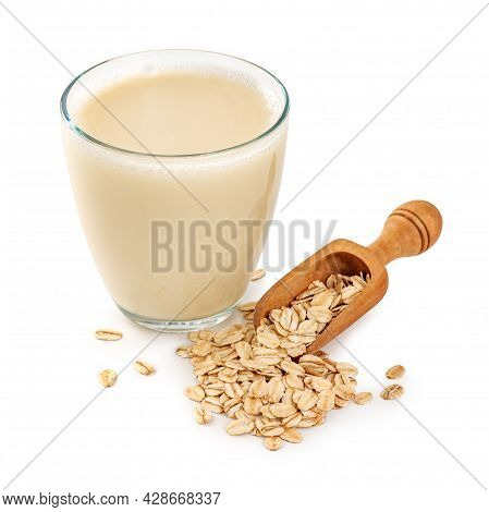 Glass Of Oat Milk With Oat Flakes In Wooden Spoon Isolated. Gluten Free Oat Milk On White Background