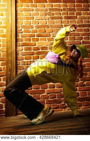Hip-hop dancer. Cool street dancer girl in bright trendy clothes and sunglasses dancing by a brick wall background.