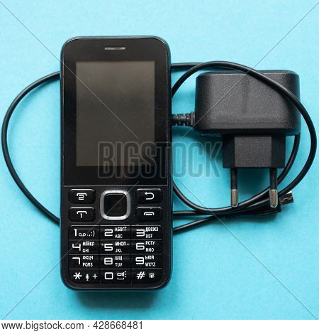 Mobile Phone And Charger On A Blue Background. Push Button Mobile Phone