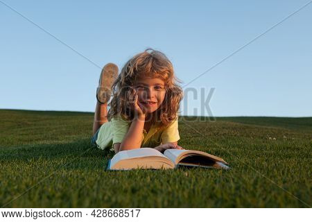 Clever Child Boy Reading Book Laying On Grass On Grass And Sky Background With Copy Space. Closeup P