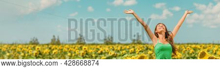 Spring happy woman with open arms walking in sunflower field enjoying free nature landscape banner panoramic. Asian girl relaxing breathing clean air outside.