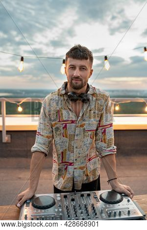 Young bearded deejay standing by soundboard in front of camera at rooftop patio