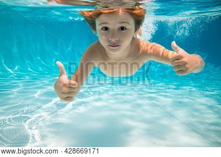 Child Swims Underwater In Swimming Pool, Happy Active Boy Dives And Has Fun Under Water, Kids Waters