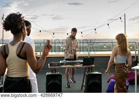 Intercultural friends dancing in front of deejay at rooftop party
