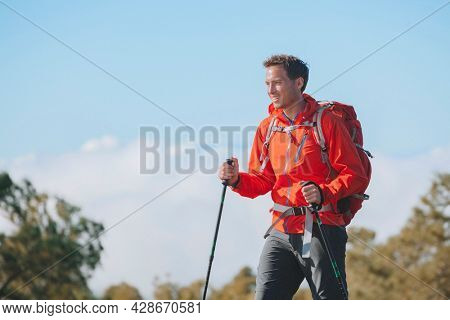 Man hiker hiking in mountain trail path on summer outdoor day wearing outerwear jacket and backpack for camping. Guy portrait lifestyle walking with hiking poles.
