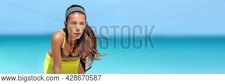 Tired running Asian woman listening to music or podcast with wireless earbuds wearing phone armband holder during beach run sweating on summer workout. Heat stroke breathing fitness girl banner.