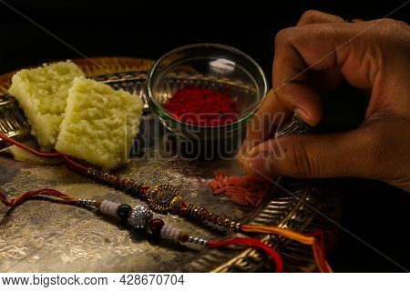 Rakshabandhan Special Sister Holding Rice To Do Tilak With A Plate Decorated With Rakhi Sweets