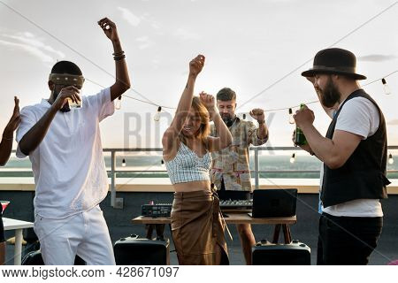 Young intercultural friends and happy deejay dancing together at rooftop party