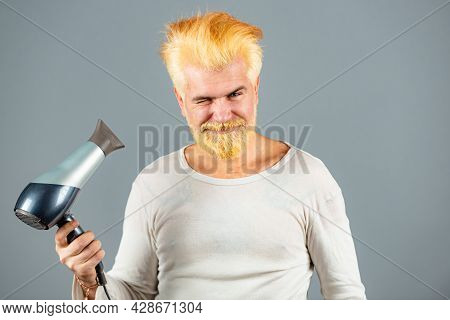 Handsome Redhead Man With Long Hair Dries His Hair With A Hairdryer. Blonde Bearded Man With Hair Dr