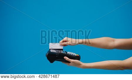 Young Girl Using Credit Card Into Credit Card Machine Or Pos Terminal Blue Background In Studio. Cop