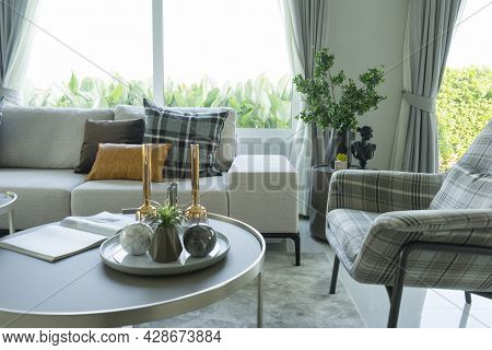 Stylish Living Room Interior With Soft Plaid Pillows And Leather Pillow On Grey Sofa.
