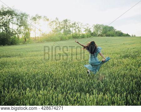 Happy Woman In Dress Running In Sunlight On Summer Field, Enjoying Life. Girl Brunette Long Black Ha