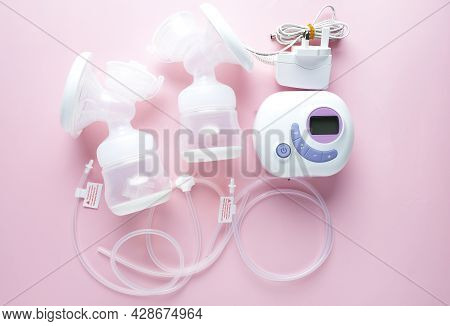 A Picture Of Portable Lactation Breast Pump On Pink Background.