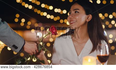 Young Asian Couple Surprise Moment With Rose Flower At Romantic Dinner In Rooftop Restaurant At City