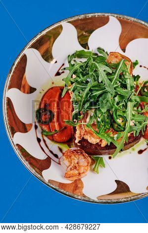 Toast With Arugula And Shrimp In A Beautiful Plate On A Blue Background. Lenten Menu. Mockup. Close-