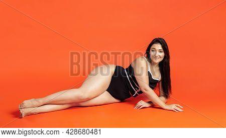 Young Beautiful Plump Woman In Black Underwear On Orange Background