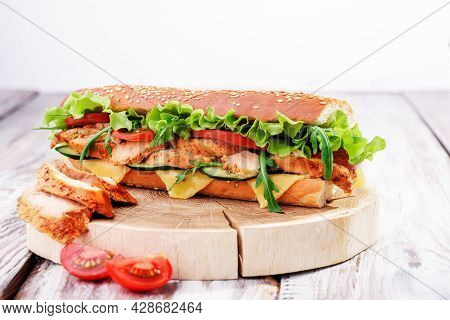 Fresh Baguette Sandwiches With Chicken, Cheese, Tomatoes And Fresh Salad, On Wooden Cutting Board On